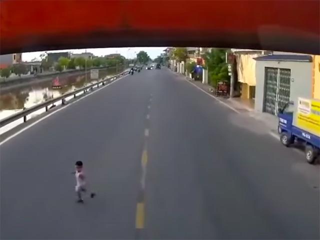 Thót tim cảnh em bé chạy sang đường băng ngang đầu xe tải