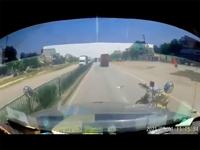 Tài xế xe máy chở hàng cồng kềnh lao vào container đang chạy cùng chiều